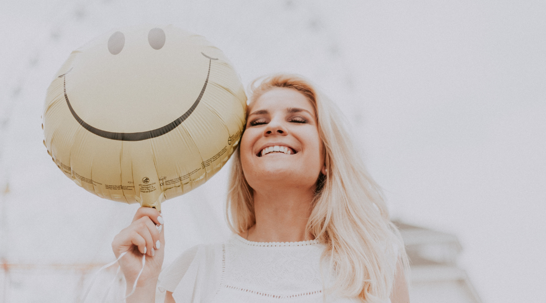 SMiling woman holding a smiley faced balloon - Libby for sexual health
