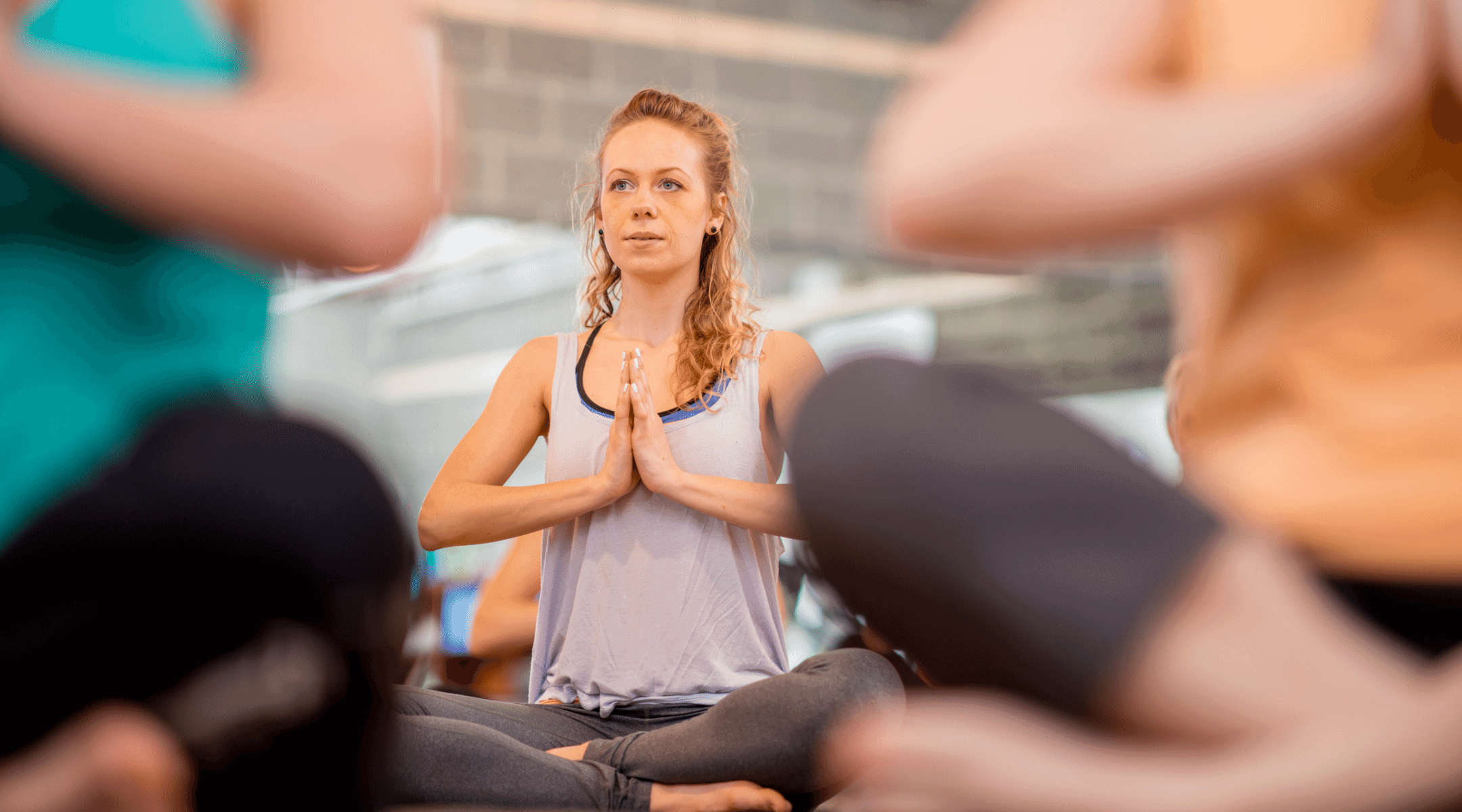 Woman sitting in a yoga pose with hands together - the link between diastasis recti and breathing