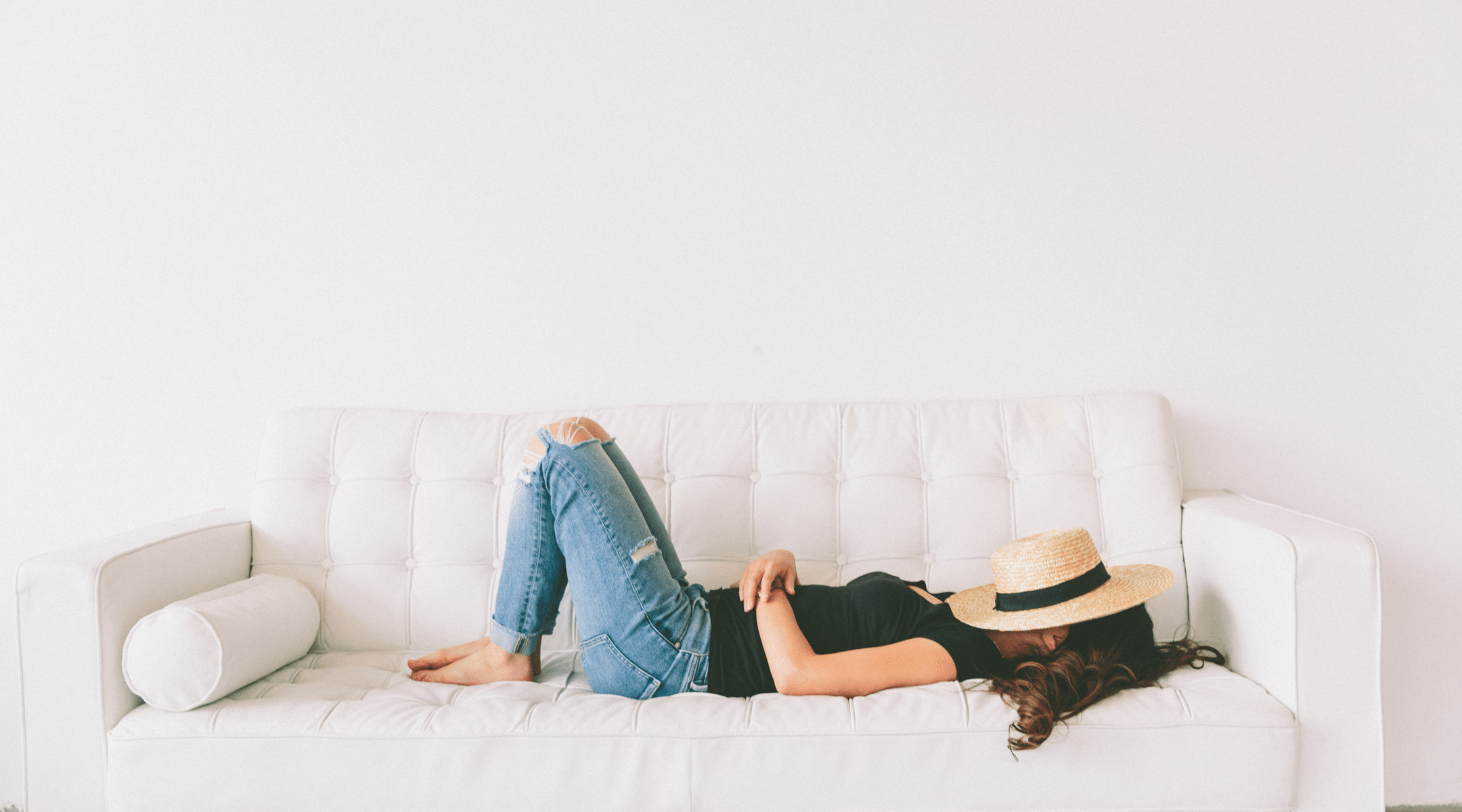 Woman laying on a sofa with a fedora over her face. Try to Relax