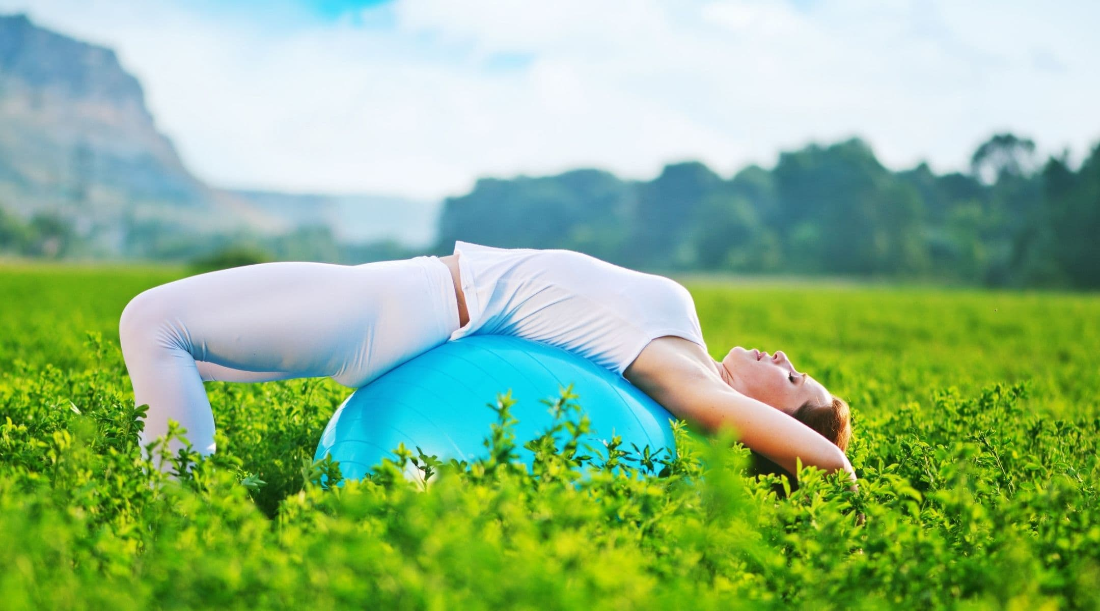 woman laying backwards on an exercise ball - 5 signs your core fitness could improve